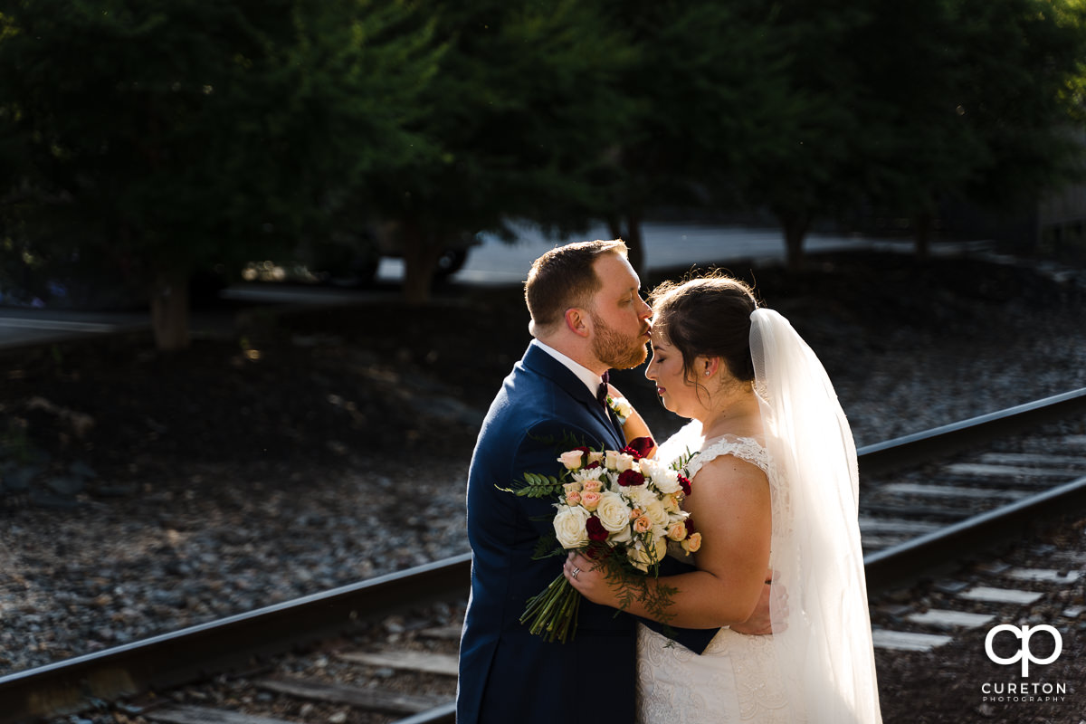 Groom kissing his bride on the forehead by the railroad tracks.