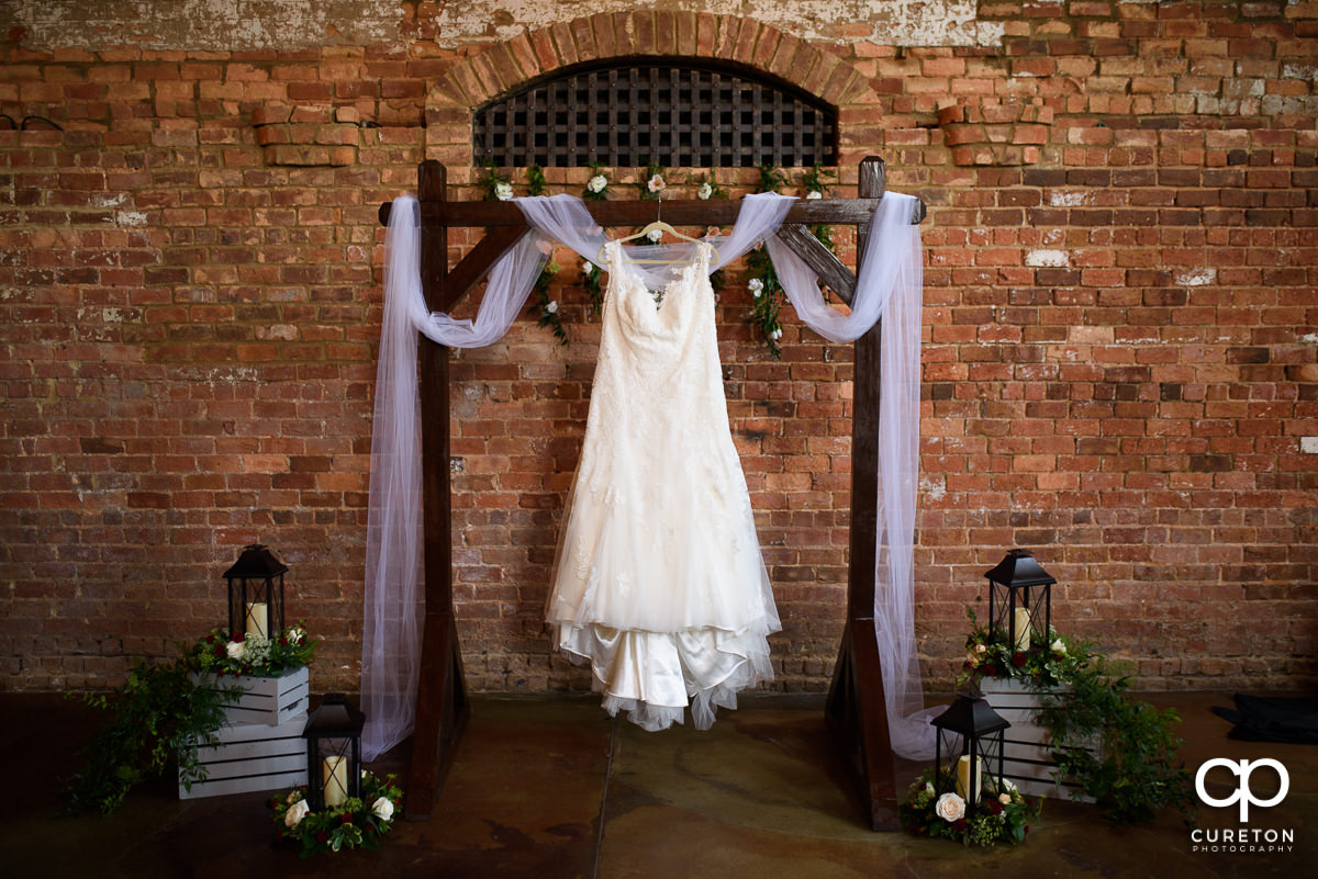 Bride's dress hanging on the alter at Old Cigar Warehouse.