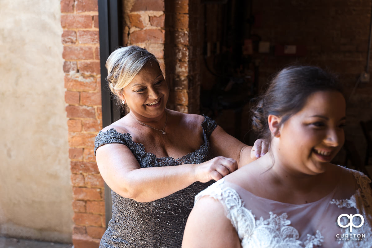 Mother of the bride helping her daughter into her dress.