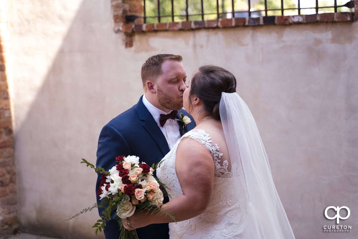 Bride and groom kissing at the first look before the Old Cigar Warehouse wedding ceremony.