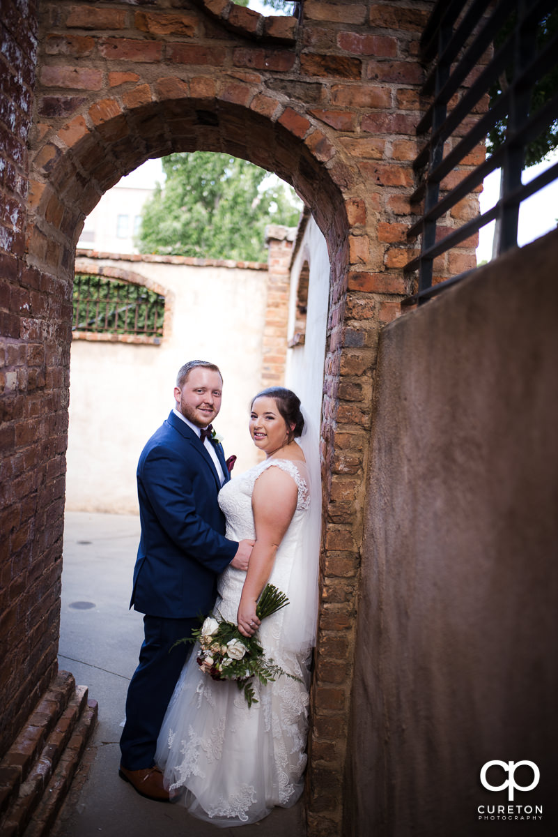 Bride and groom underneath the archway at The Old Cigar Warehouse before the wedding ceremony.
