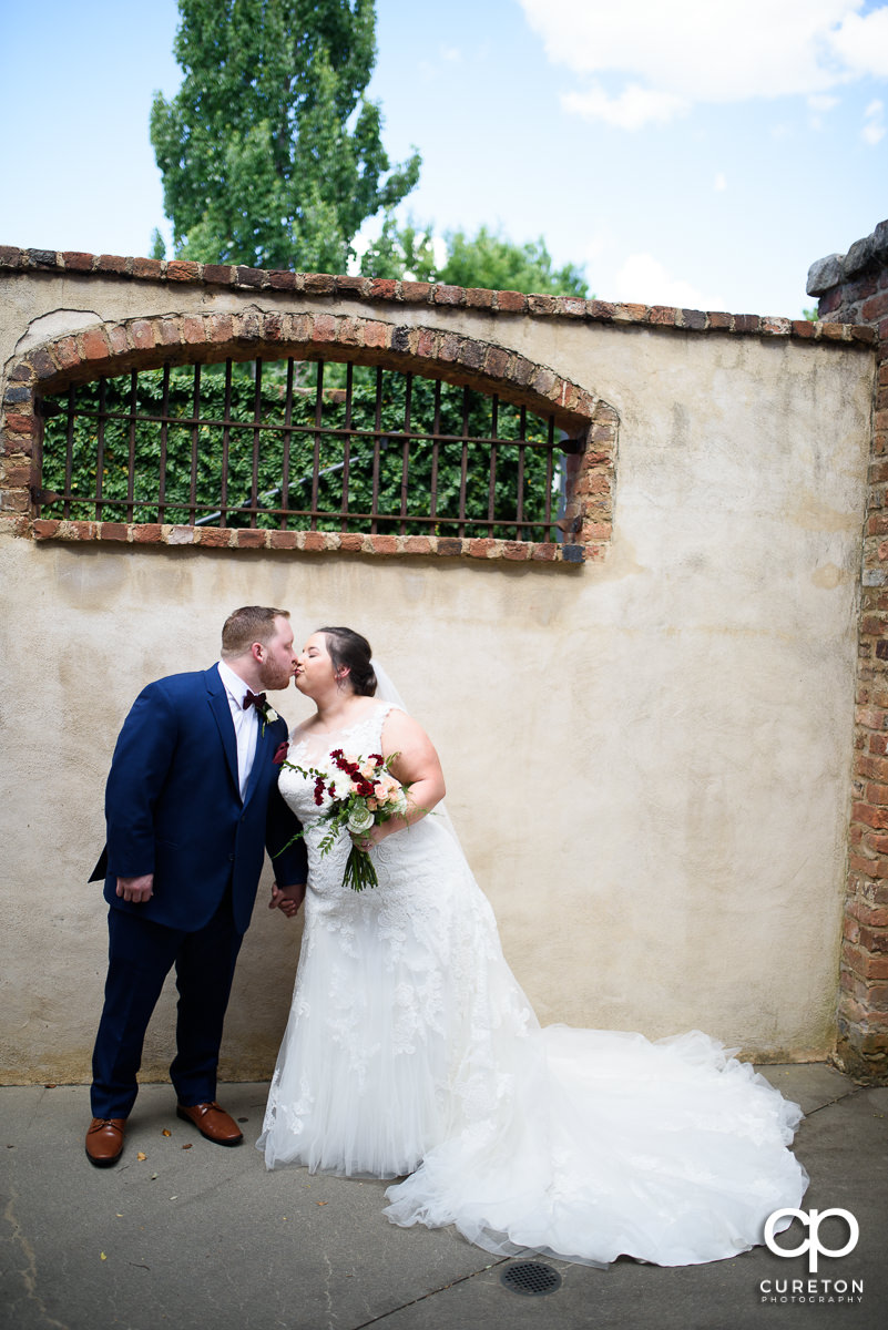 Bride and groom kissing outside of the cellar at The Old Cigar Warehouse before the wedding ceremony.