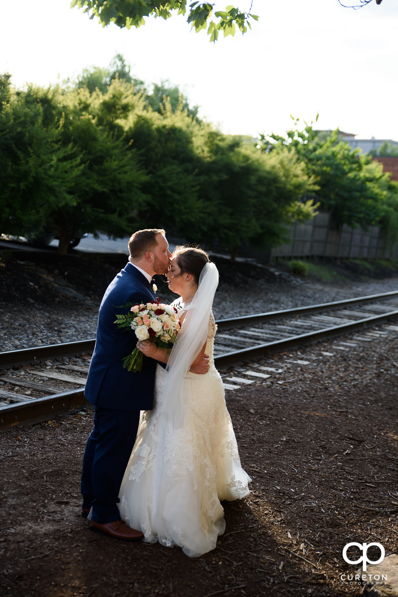 Groom kissing his bride beside the railroad tracks in downtown Greenville.