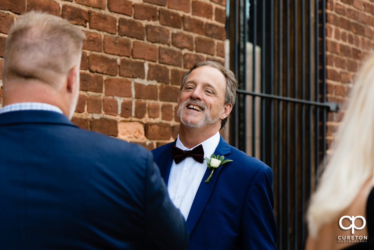 Father of the bride laughing.