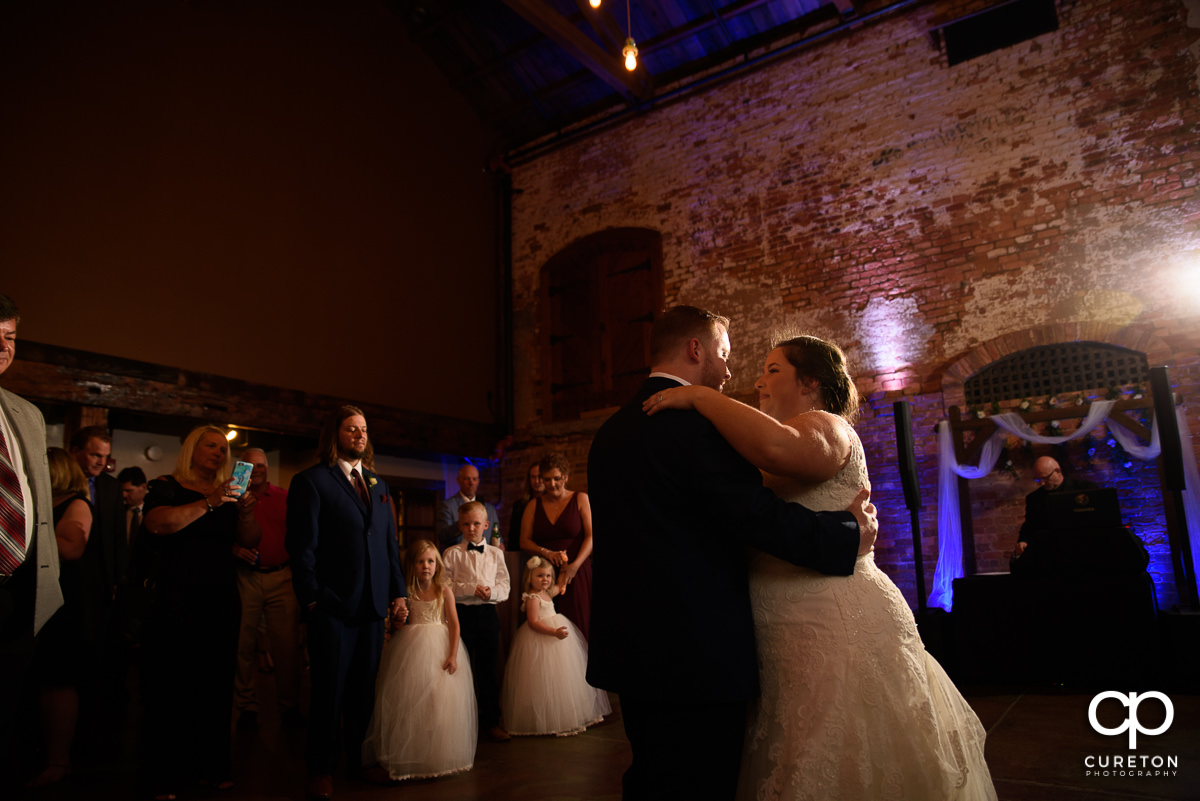 Bride and groom having a first dance at the wedding reception in Greenville at The Old Cigar Warehouse.