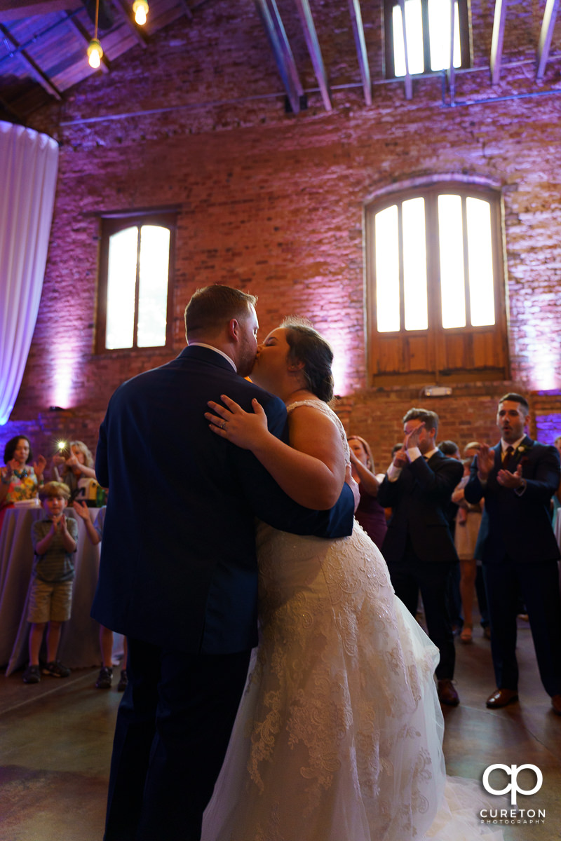 Bride and groom kissing after their first dance.