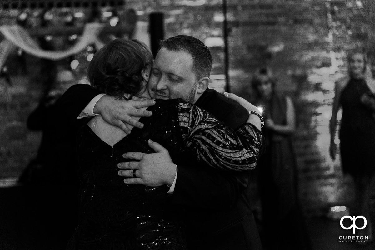 Groom hugging his mom during the wedding reception.