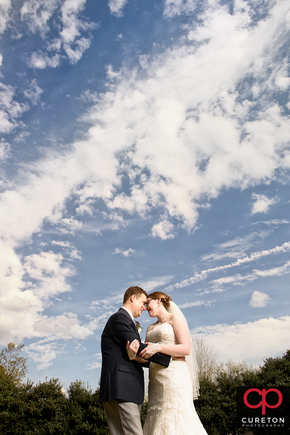 Bride and Groom under amazing clouds at thier Clemson,SC wedding.