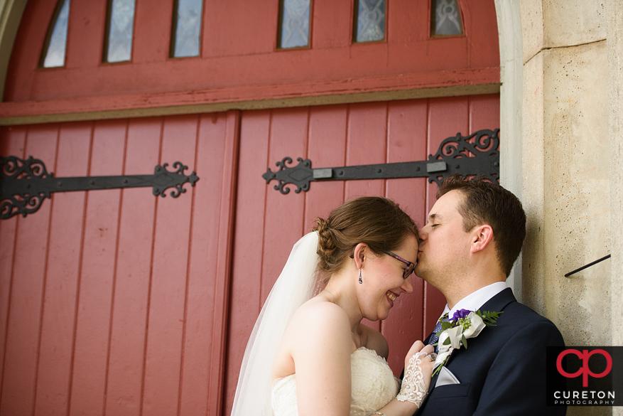Groom kissing bride's forgead.