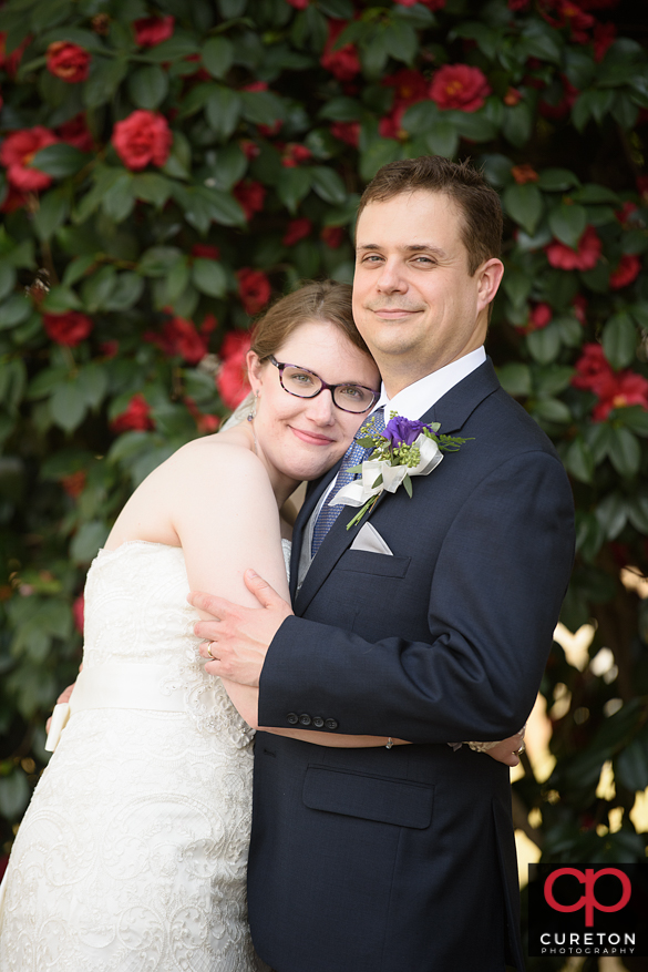 Bride and groom cuddling outside the ceremony.