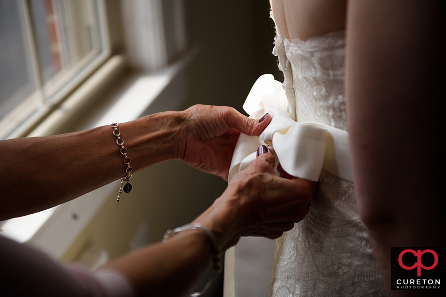 Bride's mom helping her with the dress.