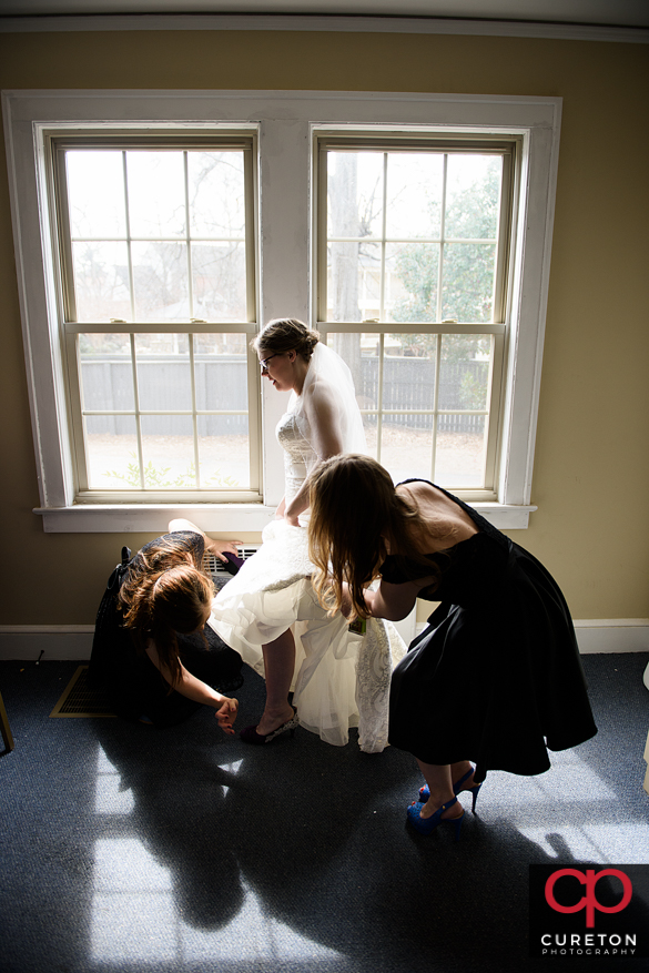 Bridesmaids helping the bride get her dress on.