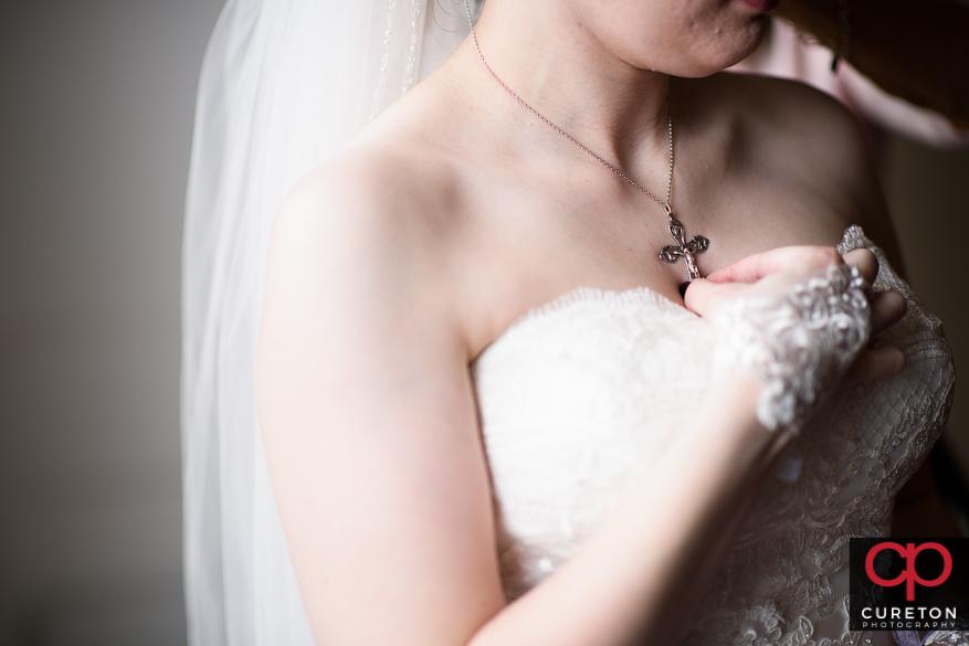Teh bride putting on jewelry.