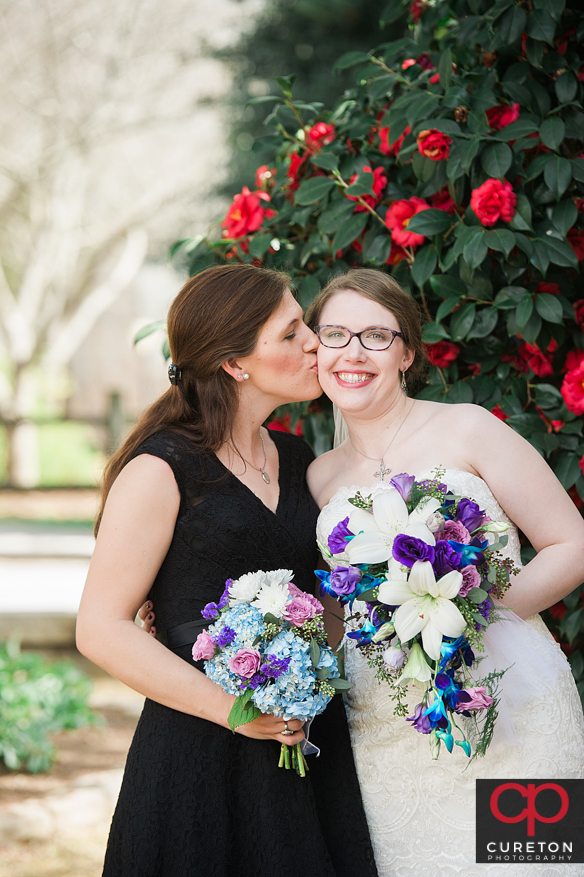 Bride's sister kissing her on the cheek.