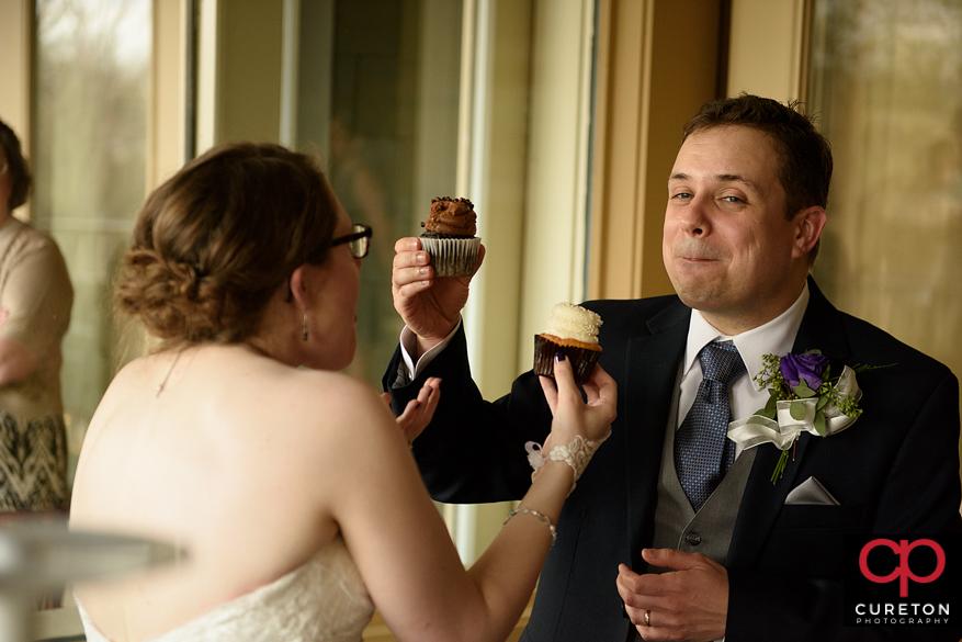 Teh bride and groom share a cupcake.
