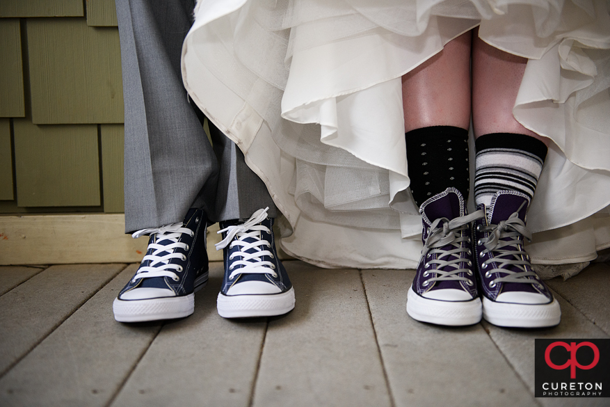 The bride and groom both wearing Converse chuck taylors.