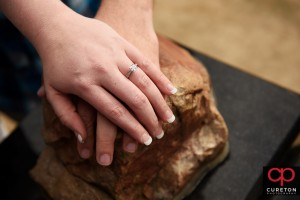 Engaged couple with hands on Howard's rock.