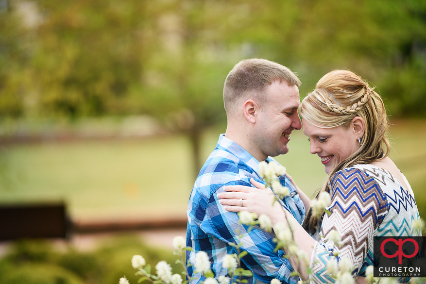 Engaged couple in the flowers near Tillman Hall.