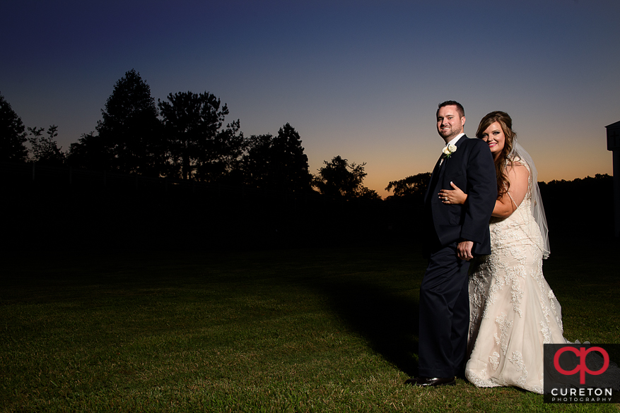 Briding groom cuddling at sunset after their Cowpens SC wedding at Mountain View Baptist..