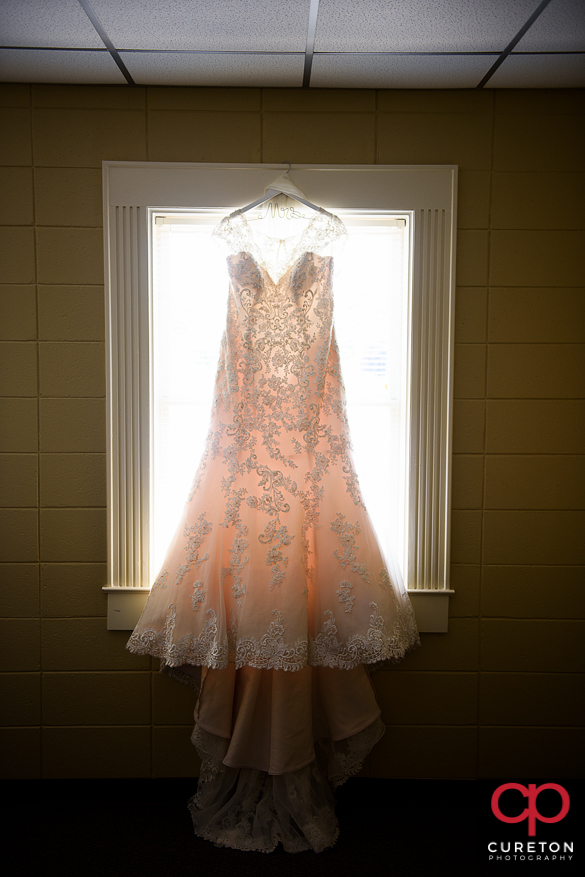 Bridal dress hanging in the window.