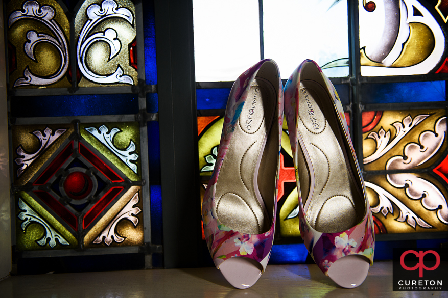 Brides shoes sitting on a stained glass window.