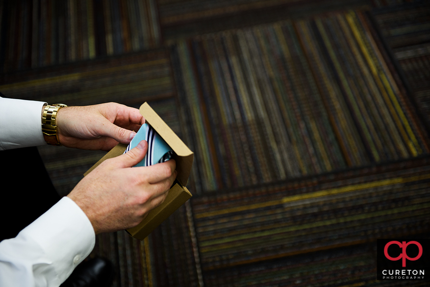 Groom holding a tie that he received as a gift from his bride.