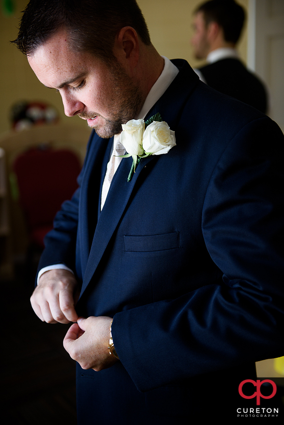 Groom fixing the buttons on his jacket.
