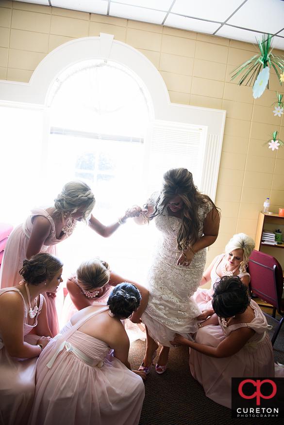 Bridesmaids help the bride fluff her dress.