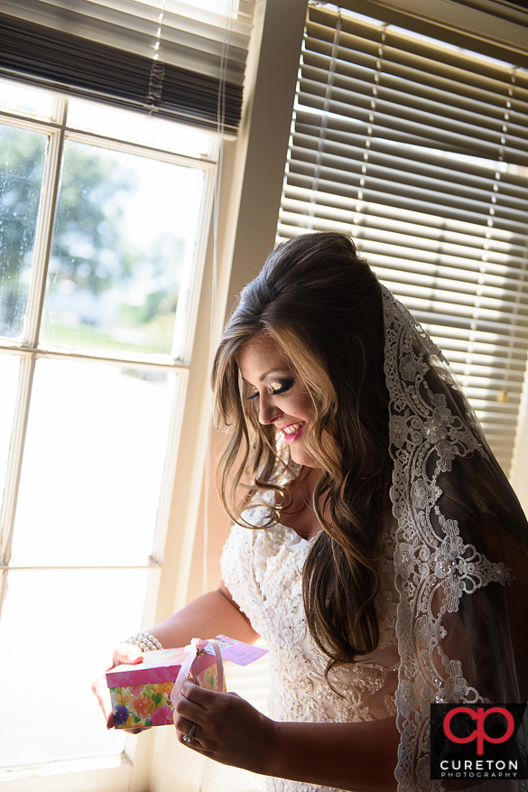 Bride opening a gift from her groom.