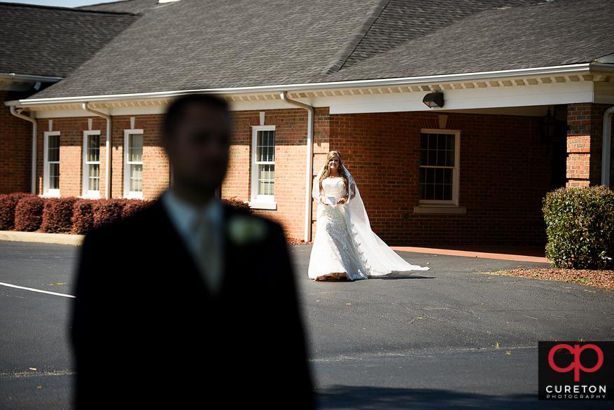 Bride walking behind her groom to the first look.
