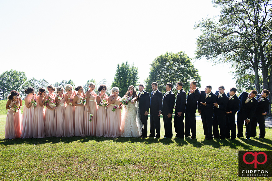 The entire wedding party looking at the brides ring.