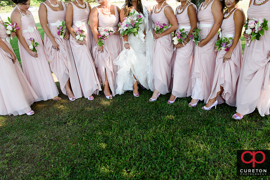 Bride and bridesmaids showing off their shoes.