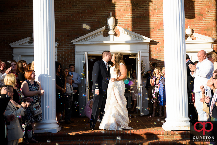 Bride and groom leaving the ceremony through bubbles.