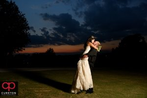 Bride and groom kissing at sunset after their Daniel chapel wedding on the Furman university campus.