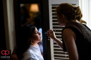 The bride getting airbrush makeup applied.