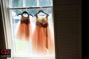 Flower girl dresses hanging in the window.