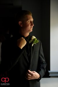 The groom straightening his tie.