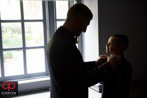 The groom fixing the ringbearers tie.