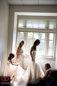 The bridesmaids help the bride into her dress.
