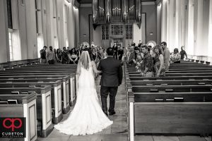 The bride and her father walking down the aisle at Daniel chapel.