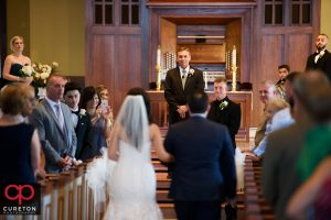 The groom sees his bride for the first time as she walks down the aisle.