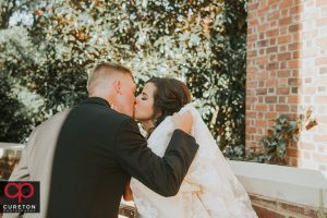 Bride and groom kissing after their wedding.