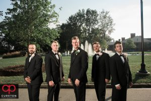 Groomsmen standing in front of the fountain at Furman.