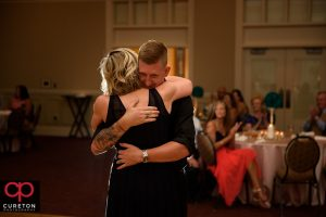 Groom hugging his mother at the wedding reception.