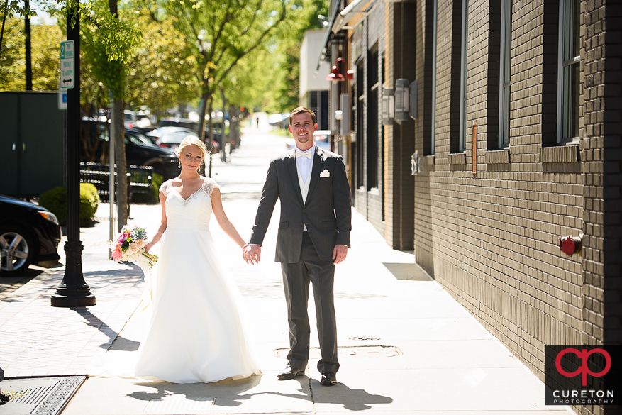 Bride and groom walking on main street in downtown Greenville,SC.