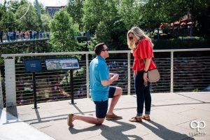 Man pulls out the ring during a surprise proposal in downtown Greenville ,SC.
