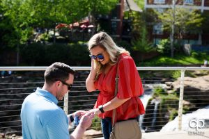Man puts an engagement ring on his fiancee's finger after a surprise marriage proposal in downtown Greenville,SC.