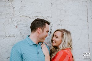 Engaged couple smiling at each other.