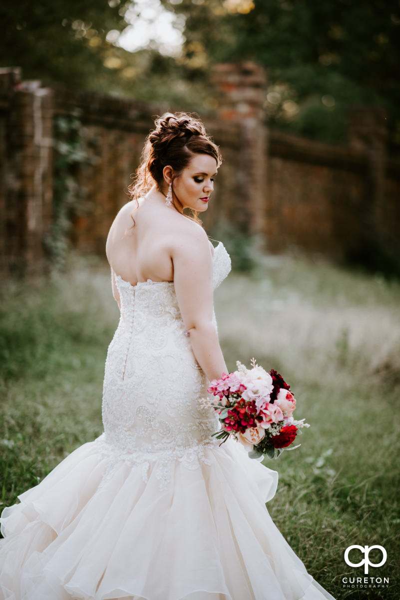 Bride standing in a field looking at her flowers.