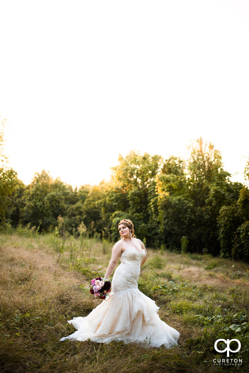 Bride in a field during golden hour at Edinburgh West.